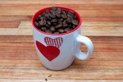 espresso coffee mug with beans on wood surface
